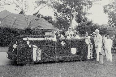 Auto geschmückt als 1. Augustwagen mit Personen. Auf dem Rücksitz, Anna Suter-Bischofberger, in Berner Tracht. Sumatra, 1. August 1931. © Schweizerisches Nationalmuseum