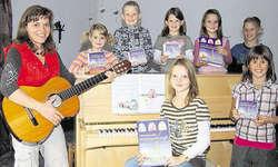 23 neue Kinderlieder komponiert: Die Komponistin Bernadette Rickenbacher-Moos mit einigen Kindern, die auf der CD als Sängerinnen mitgewirkt haben. Bild Guido Bürgler