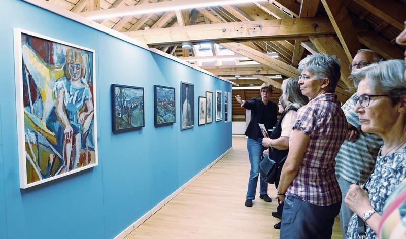 Die Besucher – darunter die Baarer Gemeinderätin Sylvia Binzegger (kariertesHemd) – betrachten die Werke. (Bild WernerSchelbert)