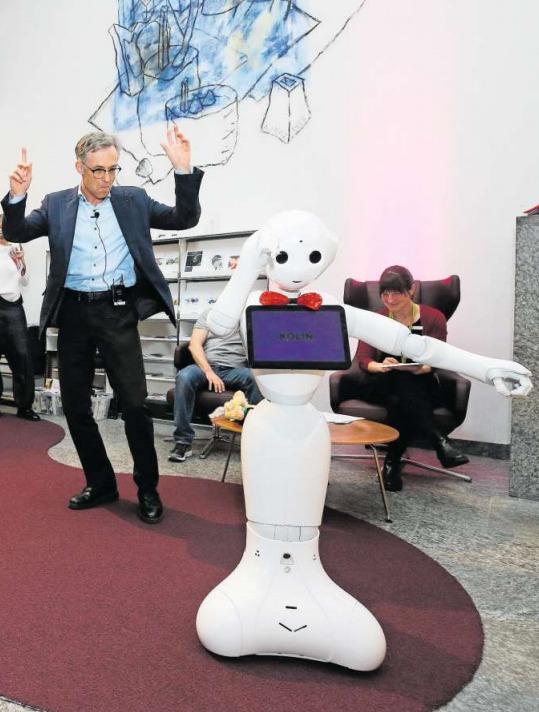 Beschwingt: Der Roboter Kolin und der Stadtpräsident Karl Kobelt führen im Foyer der Bibliothek einen Freudentanz auf. (Bild Stefan Kaiser)
