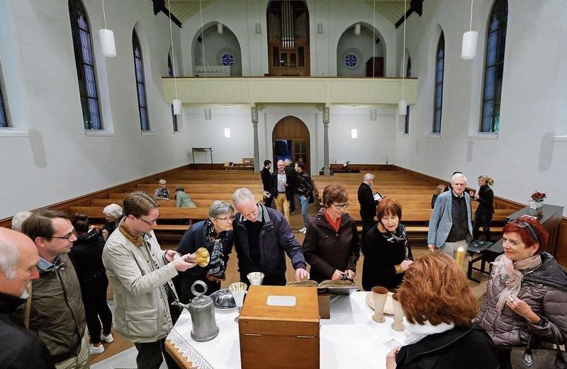 Auf kunsthistorischer Entdeckungstour: Die Besucher betrachten Objekte, die eng mit der Geschichte der reformierten Kirche in Baar verbunden sind.(Bild: Stefan Kaiser )
