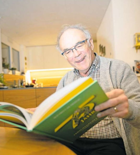 Der Verfasser Ernst Bürge begutachtet das druckfrische Jubiläumsbuch, an dem er fast zwei Jahre lang gearbeitet hat. (Bild PD/Qsi Gisler)