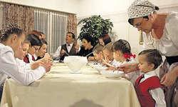 Nägelis Kinderschar bei Tisch: Unter der Obhut des strengen Vaters in der Mitte. Bild Patrick Kenel