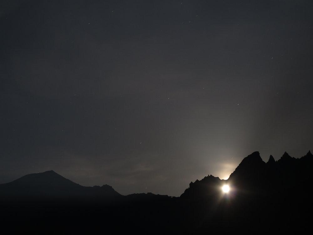 Der Mond hüllt die Berglandschaft in ein magisches surreales Licht.
