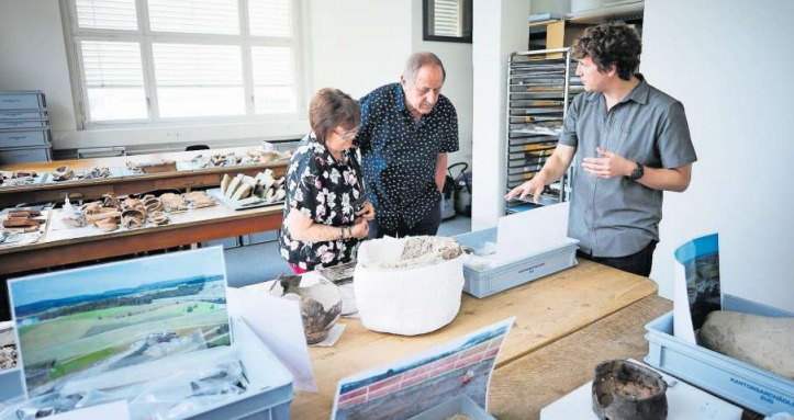 Grabungsleiter Simon Maier zeigt Josy und Silvan Romer Fundstücke aus dem Kanton Zug. (Bild Stefan Kaiser)